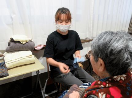 老人の話を聞く外国人介護士