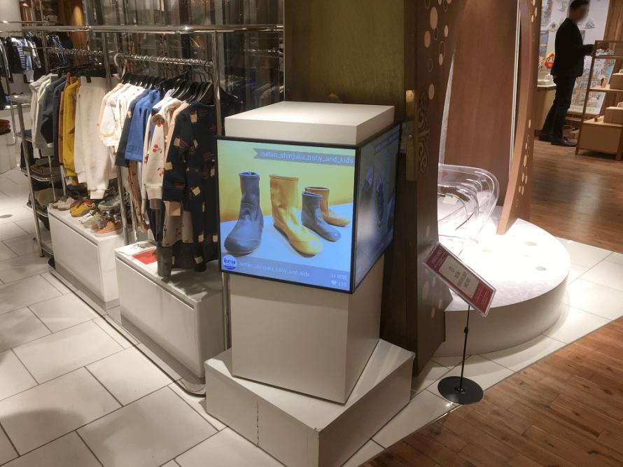 百貨店子供服売り場でSNSサイネージを使う様子